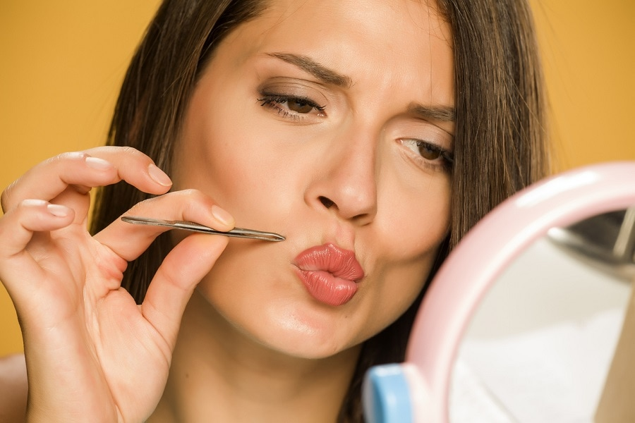 woman removing mustache with tweezers